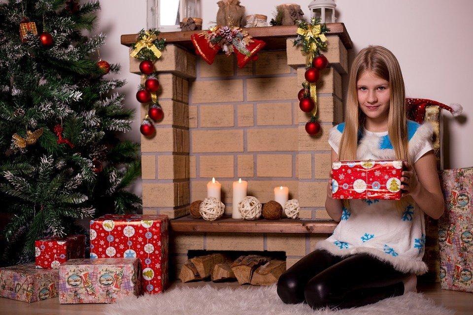 Une petite fille reçoit des cadeaux de Noël
